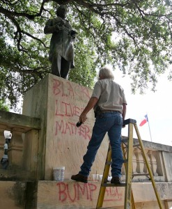 Bill Tanner with UT Facilities Services works to remove graffiti from a statue of Jefferson Davis on the south mall at the University of Texas campus in Austin, Texas, on Tuesday, June 23, 2015. (Deborah Cannon/Austin American-Statesman via AP)